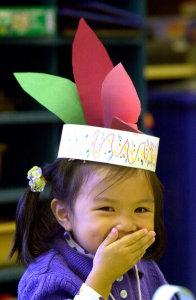 Waiting for a special lunch can be frustrating especially when it is a Thanksgiving feast but Gina Bao, 4, of Monroeville was able to pass the time adjusting her indian headband and then making a funny face in 2000. (Post-Gazette)
