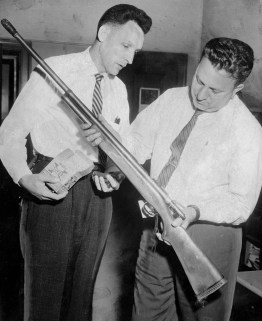 Detectives Michael Brose, left, and Lou Masters examine the shotgun used in the killing.