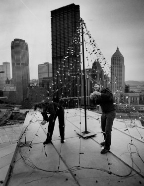 Ray Stuart, right, and Sam Lee string 300 colored lights into the shape of a Christmas tree atop the Civic Arena, Dec. 21, 1984. (John Heller/Pittsburgh Press)