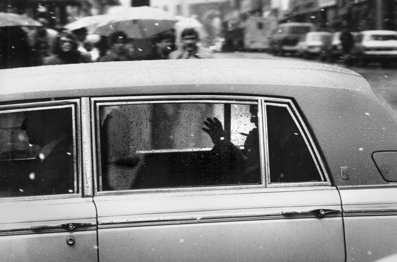 Prince Charles waves from his Rolls Royce as it rolls past Fifth Avenue and Wood Street after leaving the Duquesne Club. (Robert J. Pavuchak/The Pittsburgh Press)