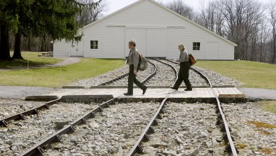 """Doug Bosley and Megan O'Malley walk over the rails leading from the replica of """"Engine House #6"""" , which was the high point of the Allegheny Portage Railroad. Two steam engines were used in each of the Engine Houses. (Darrell Sapp/Post-Gazette)"""