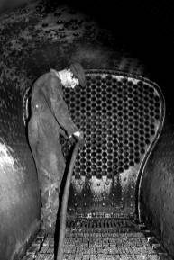 In this photo from the 1990s, Steamtown exhibit specialist Jim Reid uses an air hose to clear out accumulated cinders and spent coal that can clog the fire tubes that carry hot gases from a steam engine's coal fire through its water chamber. The procedure is still used when steam locomotives undergo a monthly boiler wash. (NPS Photo)