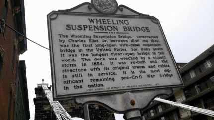 """Wheeling Suspension Bridge, built in 1849. The 1,010-foot long bridge was the first to span the Ohio River. It was blown over in a violent wind storm and rebuilt. It carries Route 40, the """"National Road,"""" over the river."""
