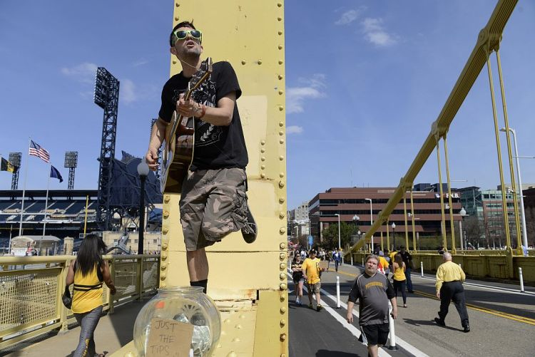 Ryan Caldwell busks on the Roberto Clemente bridge before the opening day game against the Detroit Tigers at PNC Park on the North Side Monday (Rebecca Droke/Post-Gazette).