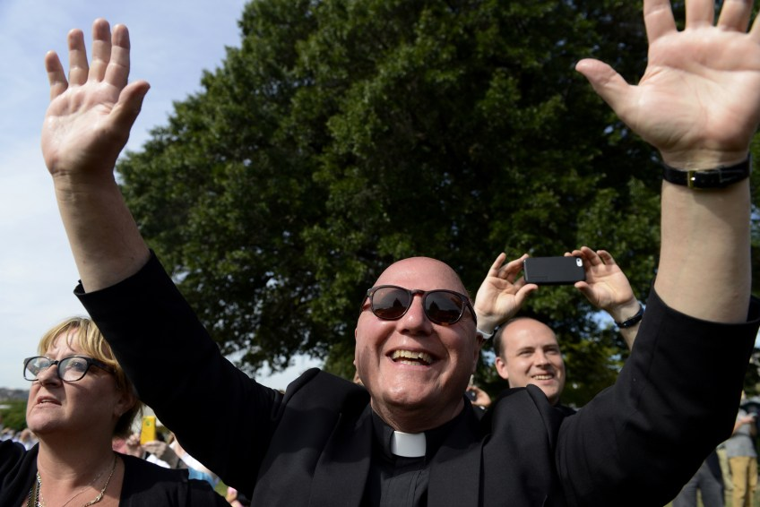 """Father Joe Mele, episcopal vicar for leadership at the Diocese of Pittsburgh, raises his arms as Pope Francis addresses the crowd from a balcony overlooking the West Front Lawn of the U.S. Capitol after Pope Francis addressed Congress on Thursday. quot;Catholics were a minority and now to see the Pope address Congress, it's really touching,"""" says Father Mele of Morningside."""