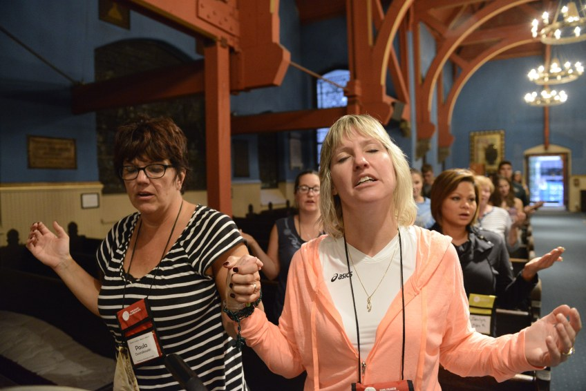 Paula Dworakowski, left, and Anne Osborn hold hands during a Mass conducted by Father Michael Roche for Pittsburgh and Erie area pilgrims  at the First Unitarian Church in Philadelphia on Friday. The women came to Philadelphia with students from Mercyhurst Prep School.