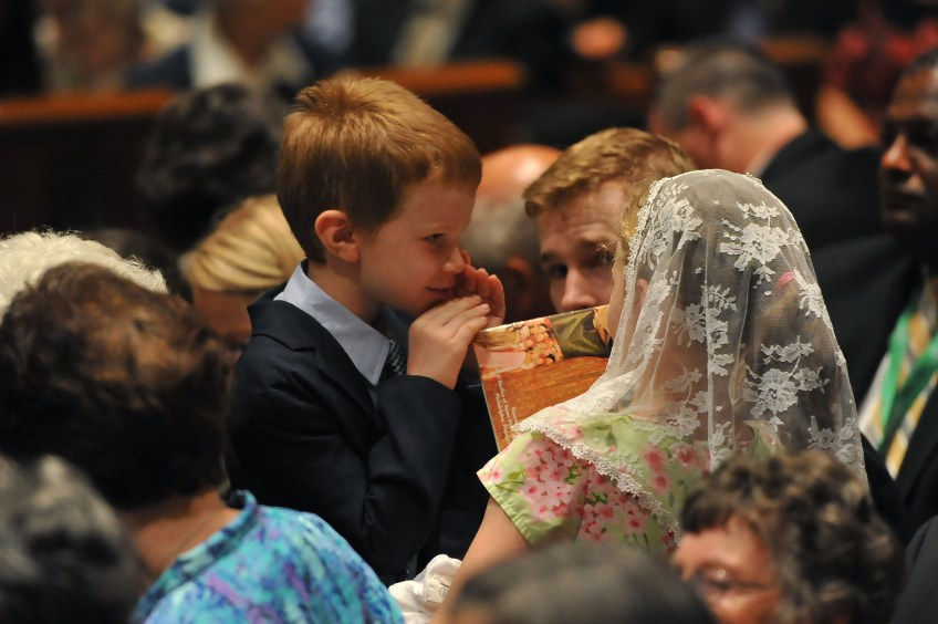 Two young Mass-goers share a moment as they wait for Pope Francis to arrive at the Cathedral Basilica of Saints Peter and Paul in Philadelphia on Saturday.