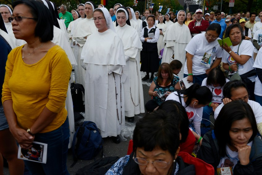 A diverse crowd listens to Pope Francis' homily including women who listen on their phones to a translation, during an open air Mass along the Benjamin Franklin Parkway in Philadelphia on Sunday, Sept. 27. (Rebecca Droke/Post-Gazette)