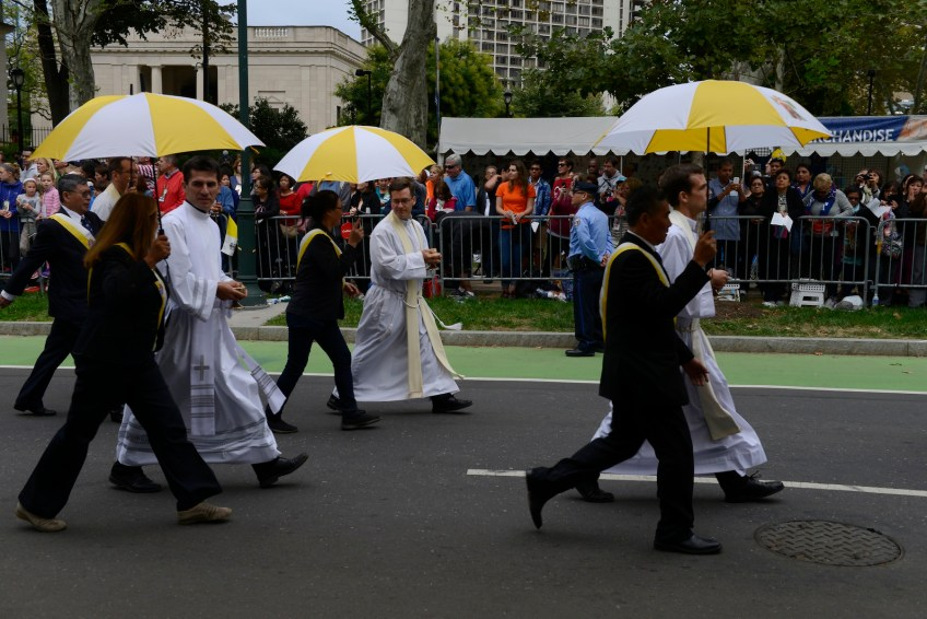 Priests are escorted along the Benjamin Franklin Parkway to give communion during an open Mass on Pope Francis' final day in the United States in Philadelphia Sunday, Sept. 27. (Rebecca Droke/Post-Gazette)