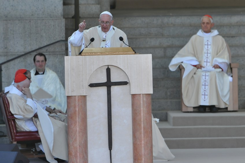 Pope Francis, left, gives his homily as Cardinal Donald Wuerl arrives at the Basilica of the National Shrine of the Immaculate Conception for the canonization Mass for Junipero Serra on Wednesday.