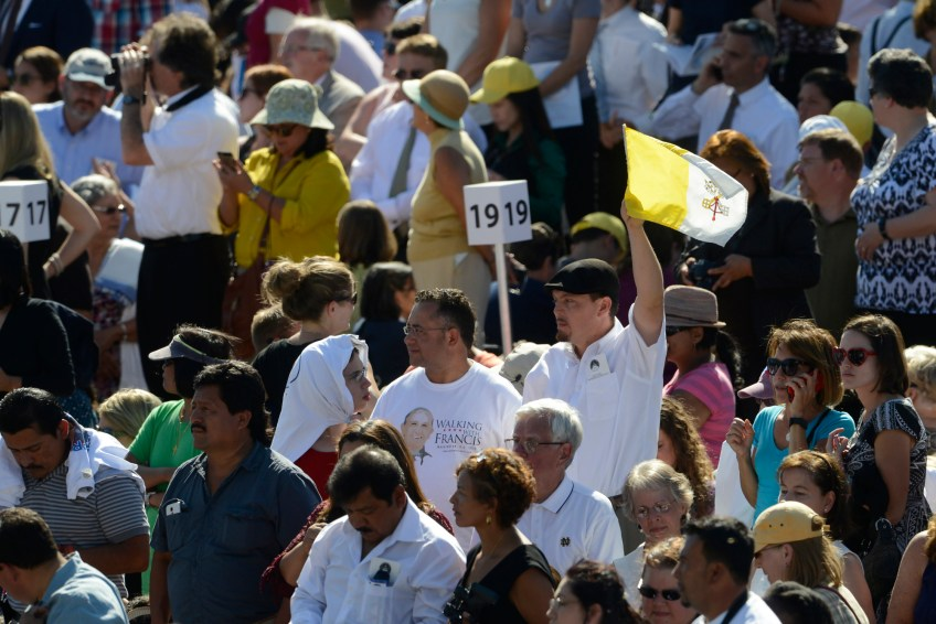 A mass-goer waves a Vatican Flag in the crowd before Pope Francis arrives at the Basilica of the National Shrine of the Immaculate Conception for the canonization Mass for Junipero Serra on Wednesday.