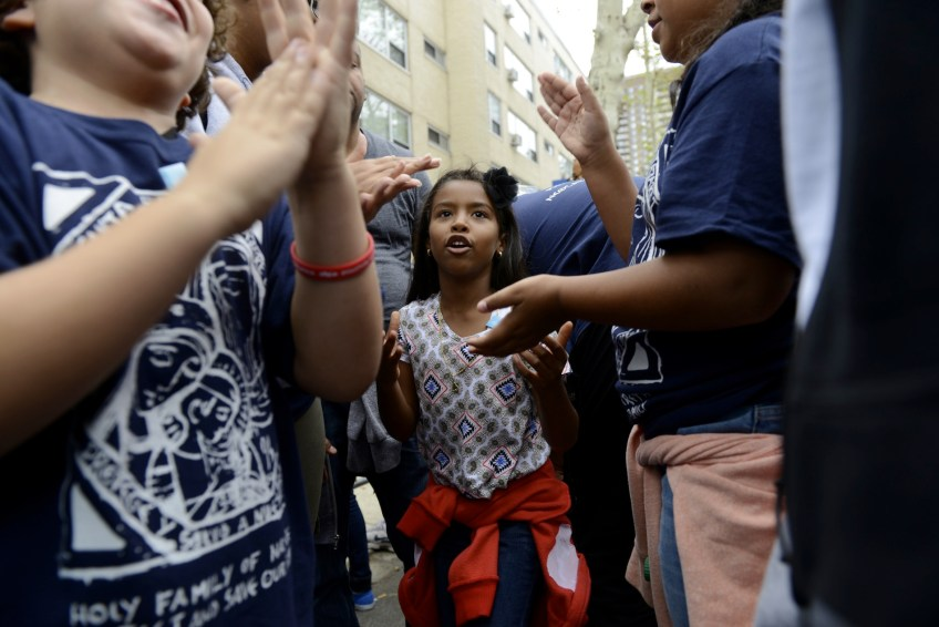Valentina Sanchez joins into Category 48, a hand game, to pass time waiting to go through security lines to attend the papal mass along the Benjamin Franklin Parkway in Philadelphia on Sunday, Sept. 27. (Rebecca Droke/Post-Gazette)