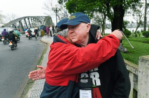 Former U.S. Marine George Haught of Monaca, facing, is comforted by good friend and fellow Marine Danny Cholewa of Benton Harbor, Michigan, Thursday Feb. 1, 2018, after crossing what is now the Truong TIen Bridge in Hue City, Vietnam. In 1968, both men along with other members of Golf Company, 2nd Battalion 5th Marines, fought their way across a previous bridge during the Battle of Hue. Mr. Haught was awarded three Purple Hearts for his service in Vietnam. (Nate Guidry/Post-Gazette)