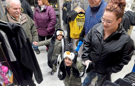 Penguins fans Josh Butenko, left, 4, of Delmont, and his twin brother Luke shop at Yinzers with family friend Dave McDowell, left, of Erie, Pa., and their aunt Sarah Calabrese  of Greensburg at the store on Friday, March 30, 2018 in the Strip District. (Lake Fong/Post-Gazette)