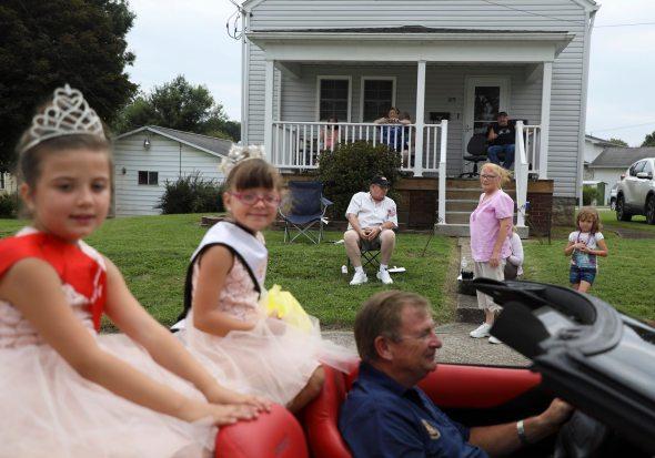 Spectators watch as Vivianna Gulino, center, the 2017-18 Little Miss Crucible, rides past during the parade. (Jessie Wardarski/Post-Gazette)