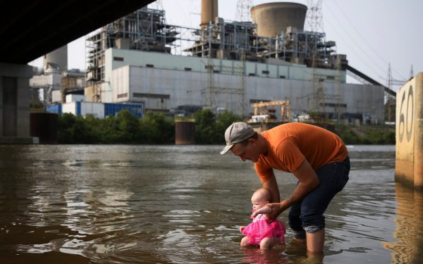 Robert Butler, of Masontown, gently lowers a friend's infant daughter into the Monongahela River on Aug. 19, in Masontown. The shuttered Hatfield's Ferry Power Station sits idle in the background. (Jessie Wardarski/Post-Gazette)