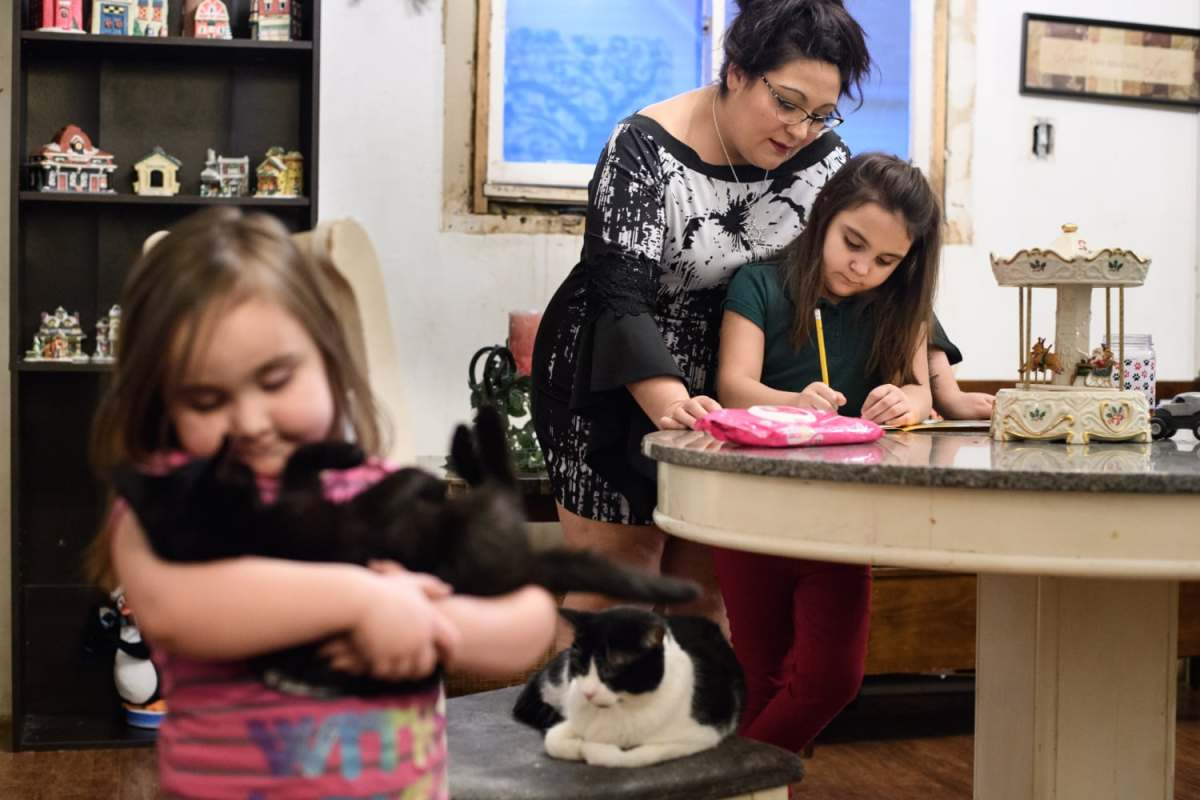 Jessica Webber helps her daughter, Kennedy Fisher, right, 7, with her homework on Wednesday, Dec. 12, 2018, at their home in McKeesport. At left is Webber's youngest daughter, Rory Webber, 4. Kennedy is back in school after Ms. Webber pulled her out when other children bullied her for bringing her late father's mementos with her.