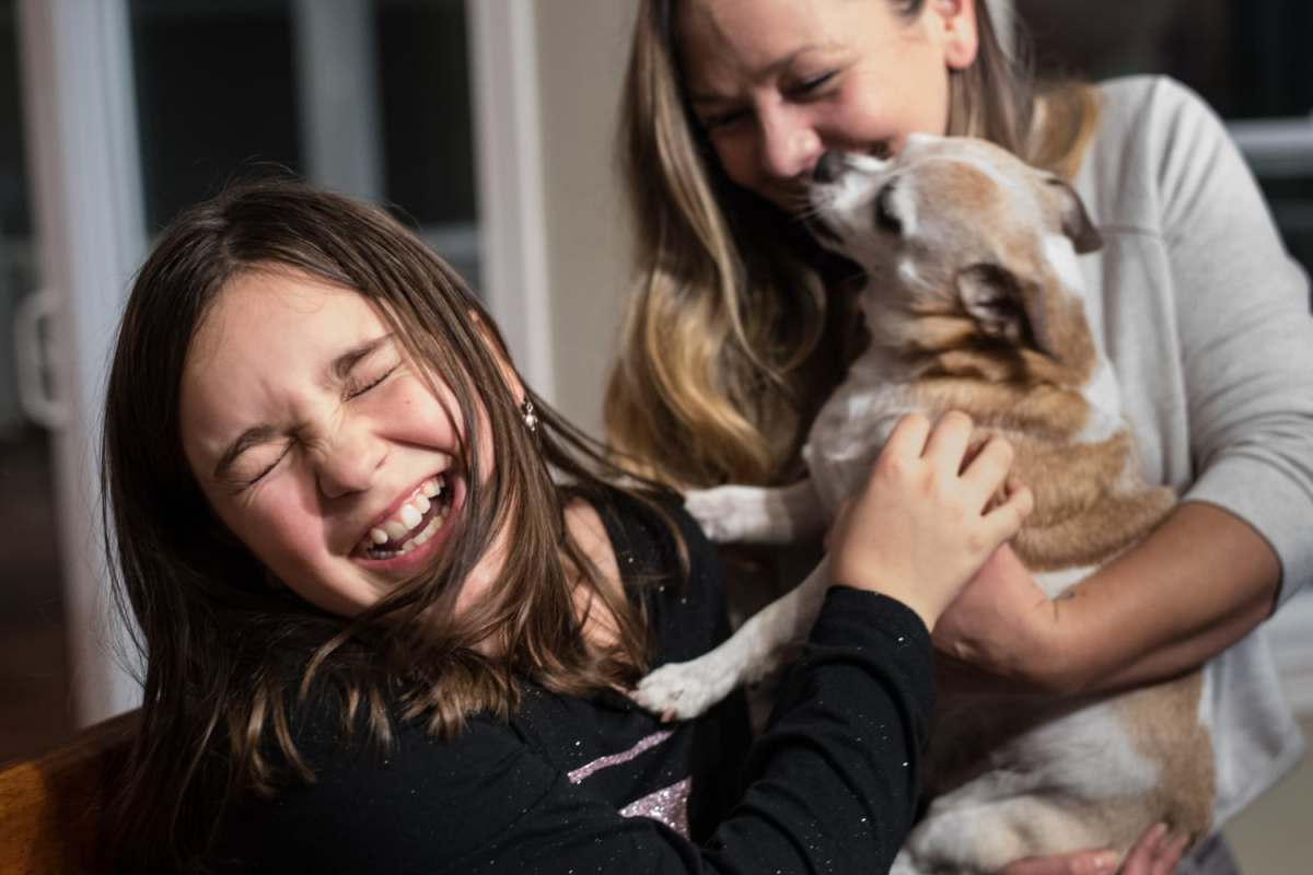 Ten-year-old Izzy Walker, left, laughs as her aunt, Maura Walker, plays with her and her dog Rooney on Wednesday, Dec. 5, 2018, at Izzy's Ohio Township home. Izzy says she likes her new school and new house after moving there after the deaths of her parents.