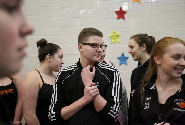 "Colby Love, center, 18, of Bethel Park holds his wrist as he and his team watch the North Allegheny swim team do a team chant before the start of the swim meet, Tuesday Jan. 29, 2019, at Bethel Park High School in Bethel Park. ""Mentally it's hard now, before it was a lot easier,"" says Love, describing what it feels like to be in the water, to swim competitively. ""Because, it's like there's nothing. It's like just your thoughts, and for me it's just hard to deal with it sometimes. Like on my bad days it's like, my brain automatically goes to my negative thoughts instead of like, I don't know, the random song that you're singing in your head."" Love describes his anxiety and depression getting bad all at the same time, in the winter of his sophomore year of high school. After taking just over a year off of both school and swimming, at which time he sought metal and physical treatment for his depression and gender reassignment, Love returned to the pool to finish his senior year in the sport."