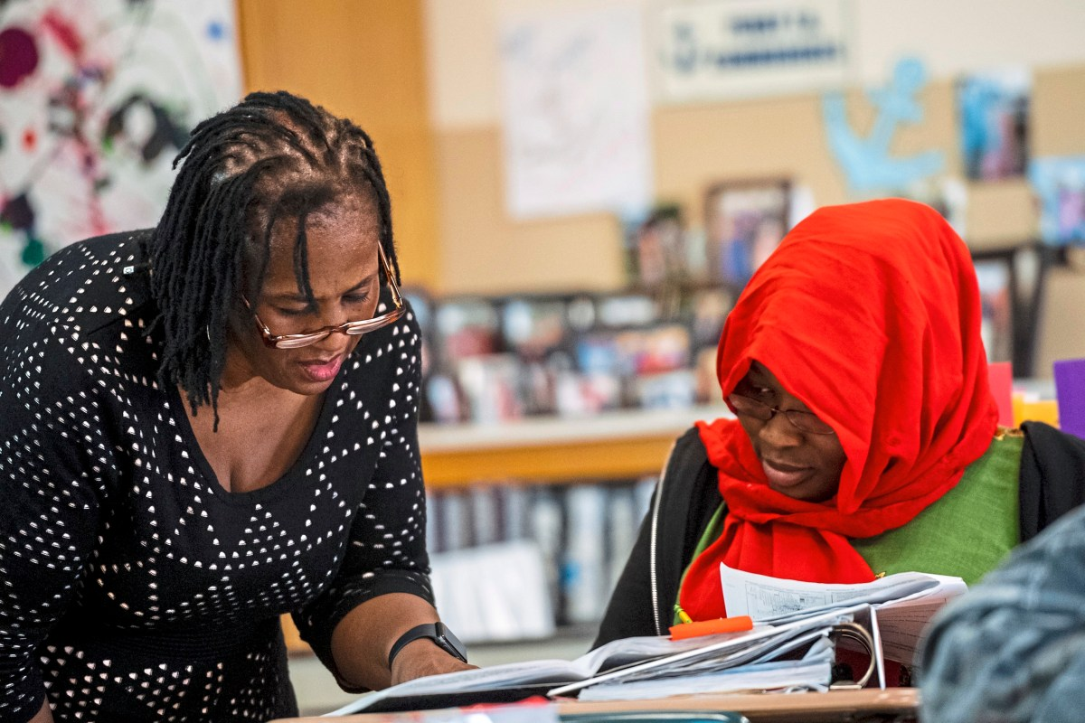 Mrs. Sharon Brentley of the North Side, left, checks the work of Gamar Muya of the North Side, right, during her tenth grade World History class, Friday, Feb. 15, 2019, at Perry Traditional Academy in the North Side. Mrs. Sharon Brentley was part of Pittsburgh Perry High SchoolÕs Class of 1977 who were the first students to attend the Northside school all four years after it formally integrated in 1973. She went back to Perry to teach and has been there for 15 years. (Michael M. Santiago/Post-Gazette)