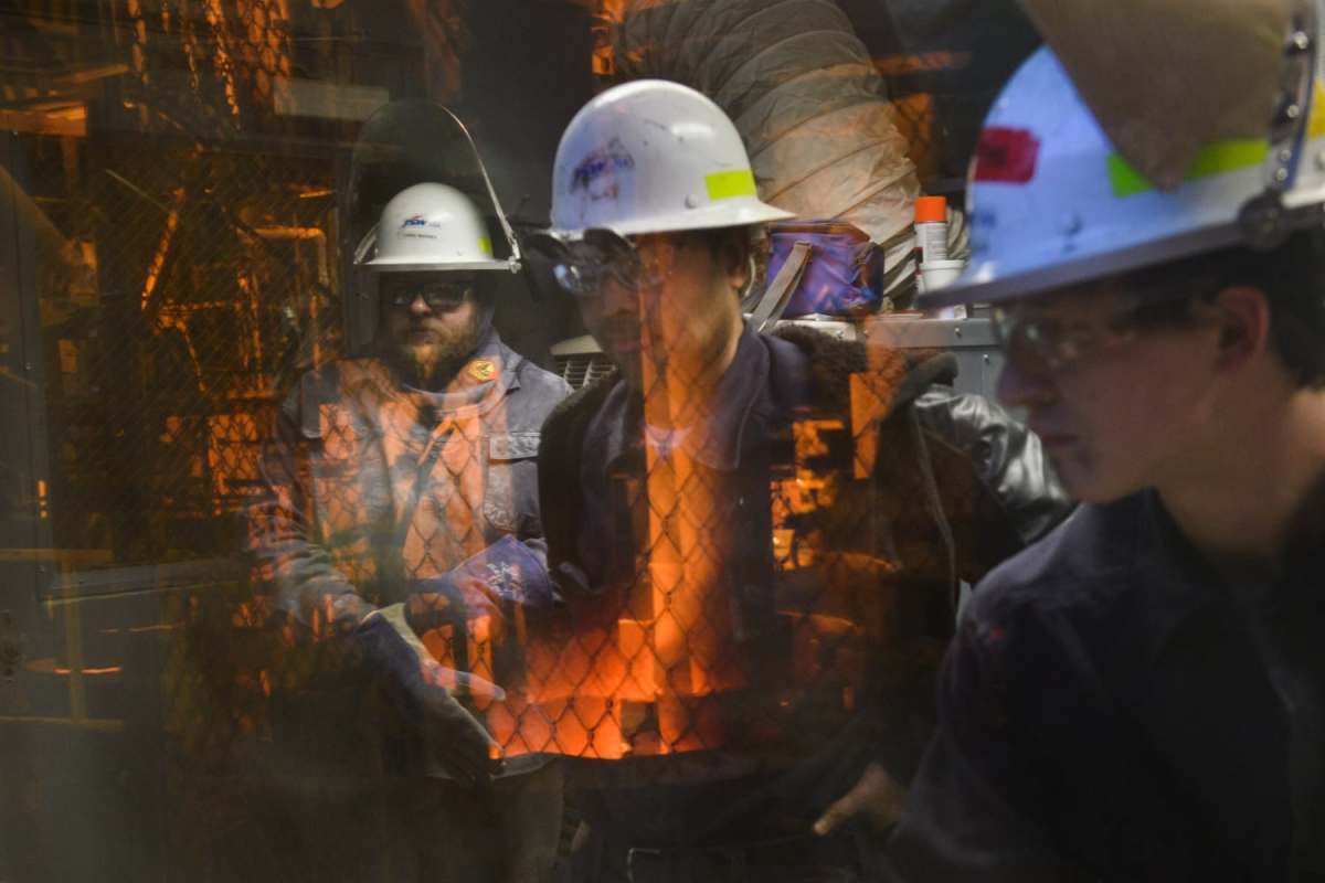 From left, Chris Barns, Dharmesh Kumar Dave and Tye Wachter, seen through  the window of the control room, work on the ladle metallurgical furnace.