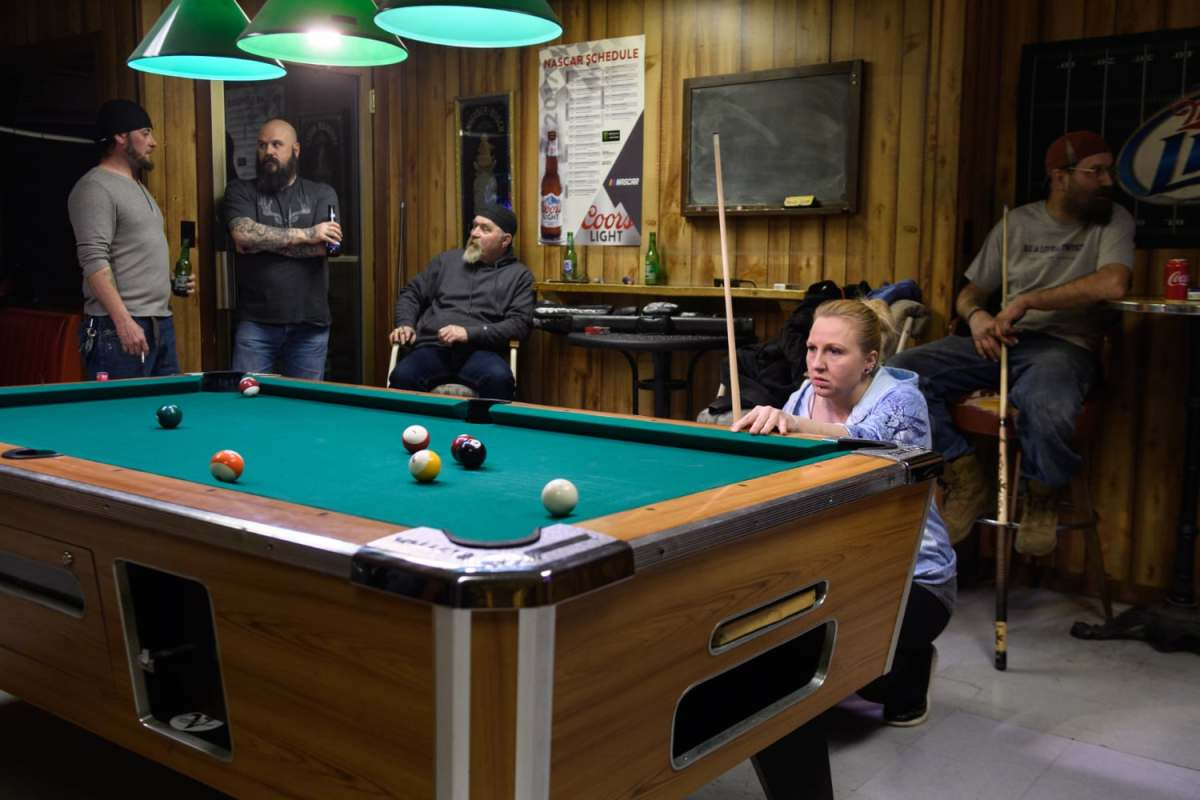 """Laborer April VanHorn, right, 40, of Mingo Junction, Ohio, shoots pool in a pool league, Thursday, Feb. 28, 2019, at Spuds Parkview Inn in Mingo Junction, Ohio. """"Everybody's hopeful,"""" said VanHorn of JSW Steel restarting the mill in town. Her father worked in the mill before it closed, and she is applying to work there as a laborer as well."""