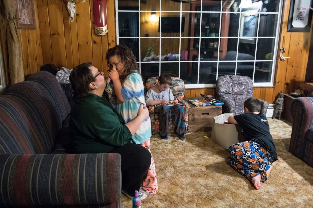 From left, Mary Beth Brown gives her daughter Nellie a hug goodnight as her sons Oliver and Anthony, 8, play before bed in April. Pain and exhaustion from Ms. Brown's breast cancer prevent her from walking upstairs to tuck the children into bed, a ritual her husband has taken over.