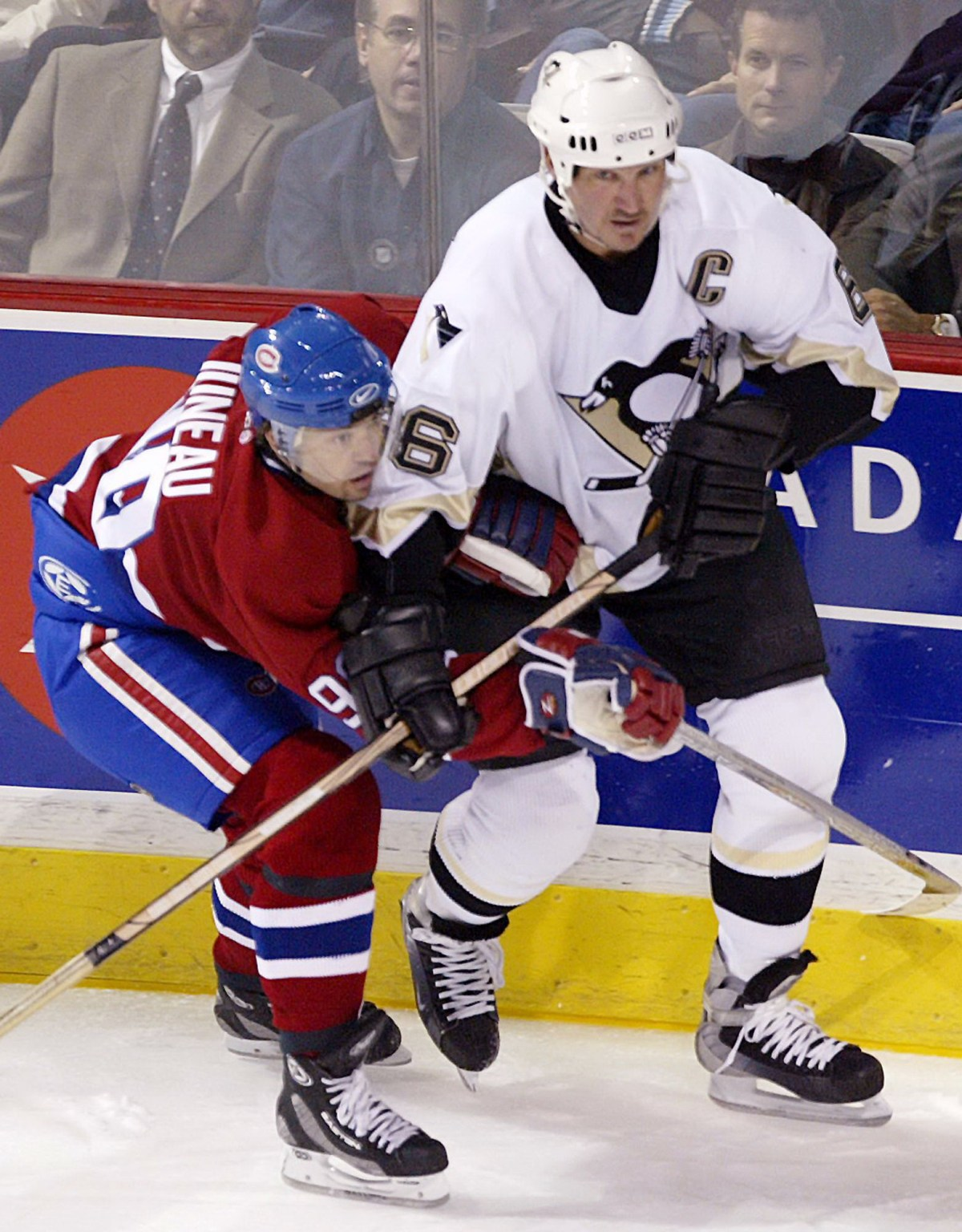 Canadiens center Joe Juneau tries to fight off Penguins center Mario Lemieux in Montreal on Thursday, Oct. 16, 2003. (Andre Pichette/Associated Press)