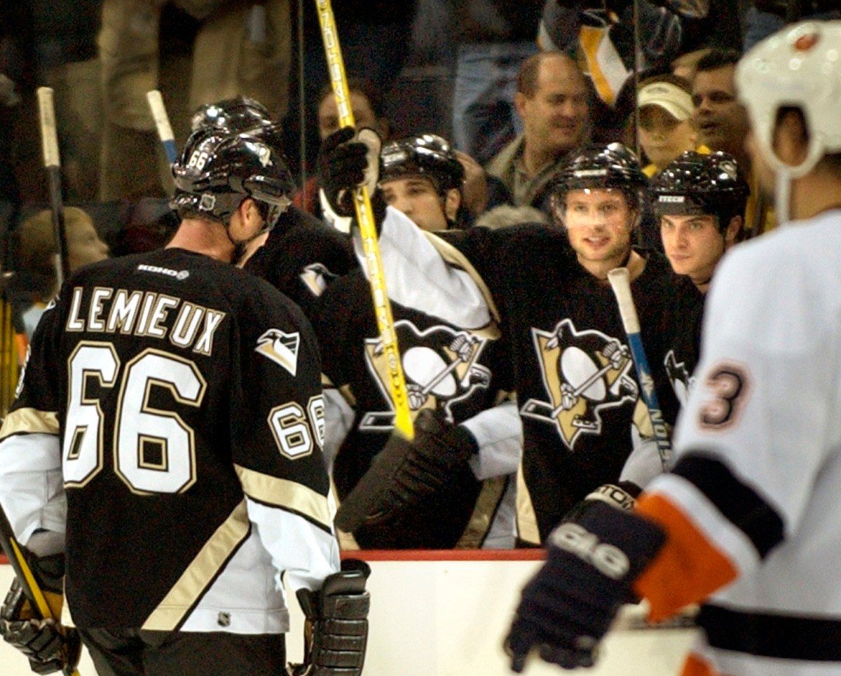 Alexei Morozov celebrates with teammates as Mario Lemieux skates to the bench after recording his 1,700th assist on Oct. 29, 2003, against the New York Islanders at Mellon Arena. (Peter Diana/Post-Gazette)
