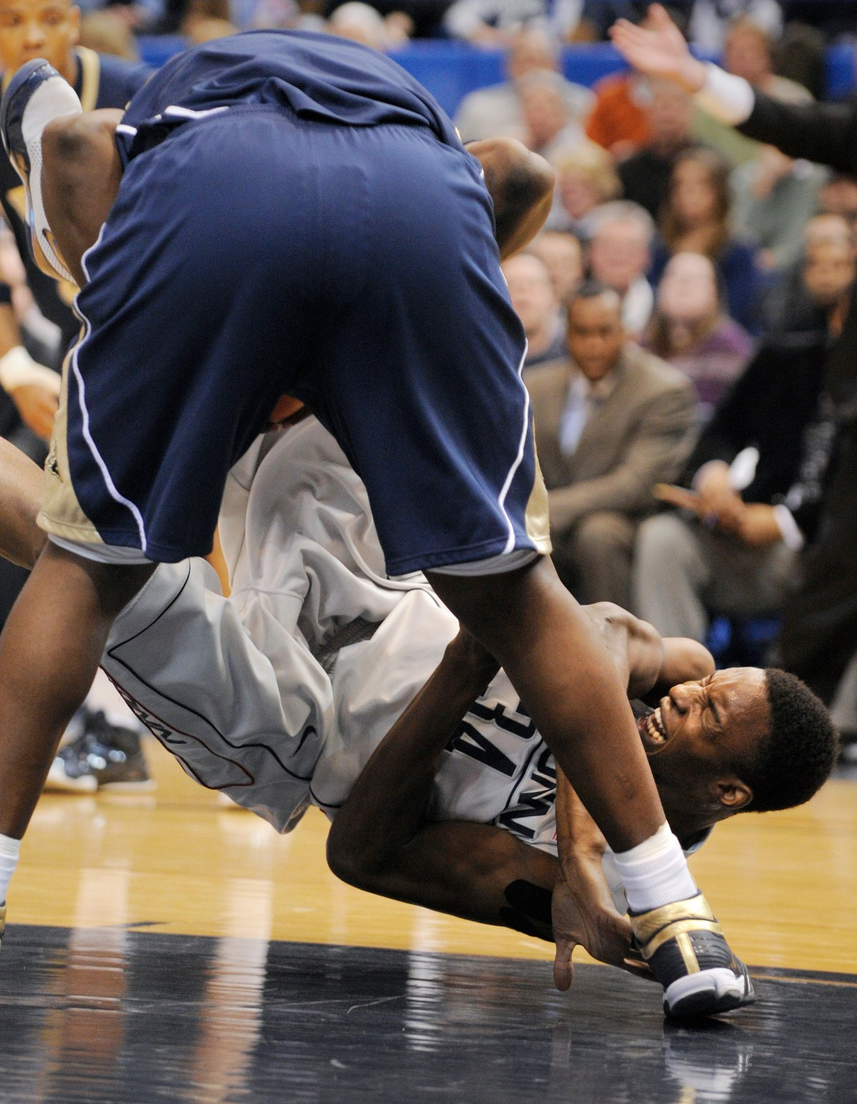 Connecticut's Hasheem Thabeet lands hard after attempting a rebound against Pittsburgh's DeJuan Blair during the first half of an NCAA college basketball game in Hartford, Conn., on Monday, Feb. 16, 2009.  (AP Photo/Fred Beckham)