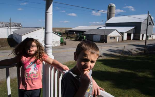 Nellie Brown, left, 6, lounges on the porch bannister as her brother Oliver, 7, fumbles with a set of toy teeth, Wednesday, April 3, 2019, at their family farm straddling Saltlick and Bullskin in Fayette County. Behind them, the milkbarn where their father milks 50 to 60 head of cattle twice a day. His family has lived on the farmland since the 1700s.