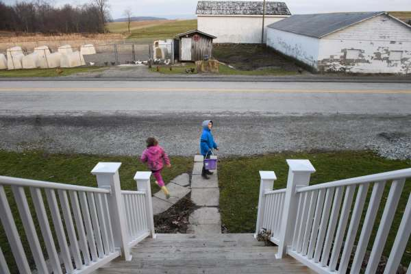 "Nellie Brown, left, 6, and her brother, Oliver, 7, head out to do their chores after school, Thursday, Jan. 3, 2019, on their family farm that straddles Saltlick and Bullskin. ""Part of the reason we don't feel poor, is you look cross the mountain, and it's gorgeous. It's beautiful,"" says the children's mother, Mary Beth Brown."
