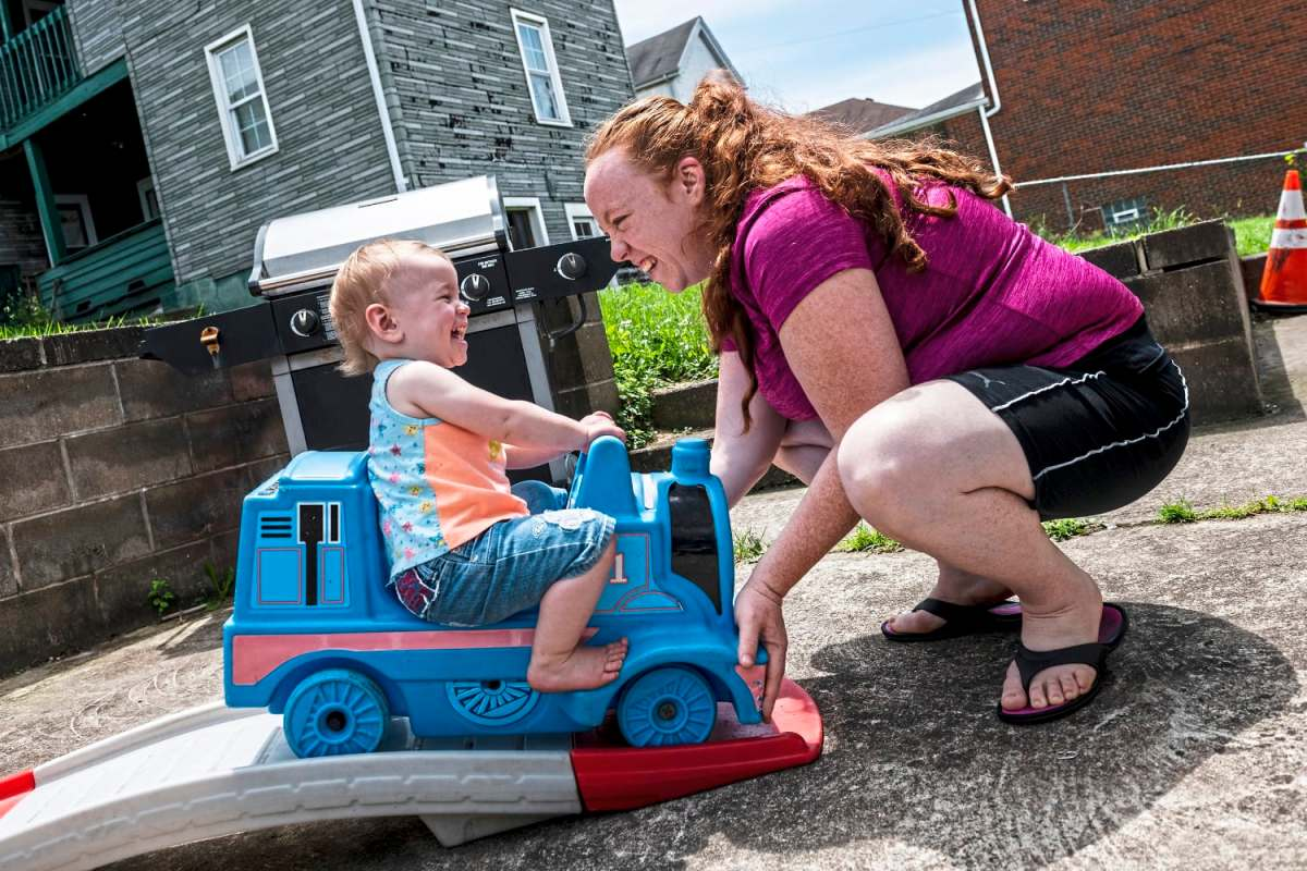 Karlee Brydges, 1, laughs as she is pushed by her mother Rebecca Brydges while riding a toy train, Saturday, June 8, 2019. Issues with peeling paint and mold in their McKeesport home prompted Ms. Brydges to move her family to Glassport. Her kids now will attend the South Allegheny School District, which she believes will better serve her 5-year-old son Jaxen, who is autistic. (Michael M. Santiago/Post-Gazette)