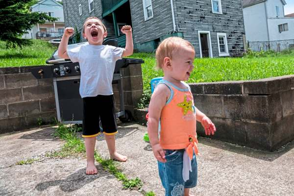 Jaxen Jakub, 5, of Glassport, left, celebrates after dunking a ball in a toy basketball hoop as his sister Karlee Brydges, 1, of Glassport, right, walks away laughing in the backyard of their mother new home, Saturday, June 8, 2019, in Glassport. (Michael M. Santiago/Post-Gazette)