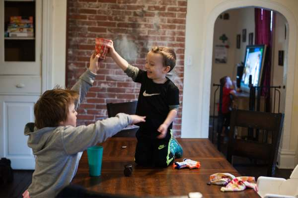 Sean Brydges, left, then 9, tries to control his younger brother, Andre Jakub, 3, as he dangles a cup above Sean's head on Sunday, Feb. 24, 2019, at their home in McKeesport. At back right, their brother Jaxen Jakub, 5, watches television. (Stephanie Strasburg/Post-Gazette)