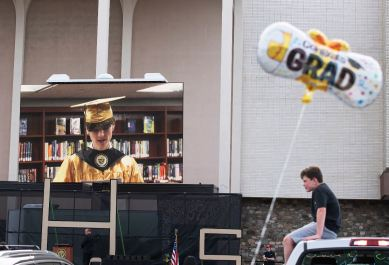 A recorded welcome address by Donovan Baxter, the Gateway senior class president, plays on screen during Gateway High School's graduation ceremony, Wednesday, May 27, 2020, in the Macy's parking lot at the Monroeville Mall. (Emily Matthews/Post-Gazette)