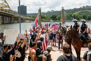 "Police on horseback sit between participants of the ""4th of July Trump Boat Parade & Salute To First Responders"" and event counter-protesters, Saturday, July 4, 2020, on the North Shore. The flotilla of President Trump supporters held a parade down the Monongahela River despite Allegheny County's prohibition against gatherings of more than 25 people, announced in an attempt to control surging COVID-19 cases. (Emily Matthews/Post-Gazette)"
