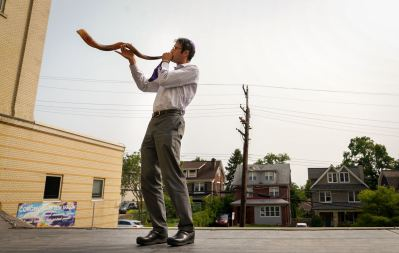 Rabbi Seth Adelson of Congregation Beth Shalom blows a shofar from the roof of the synagogue's early learning center, Tuesday, Sept. 15, 2020, in Squirrel Hill South. The horn is typically blown during weekday morning prayer in the month leading up to Rosh Hashanah, but since services moved online due to the pandemic, Rabbi Adelson's effort provided an opportunity for those wanting to hear the shofar in person. (Steve Mellon/Post-Gazette)