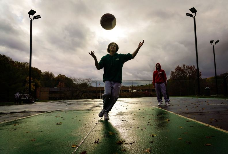 Jack Krebs, 15, joined friends, including Nolan Smith, 14, right, in a game of chilly and wet basketball, Friday, Oct. 30, 2020, in Mt. Lebanon. (Steve Mellon/Post-Gazette)