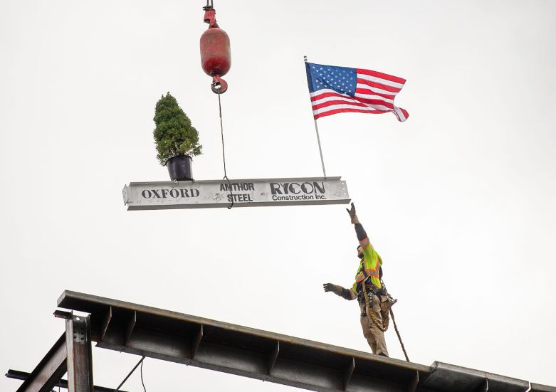 "A worker from Abate & Irwin reaches for the ceremonial ""topping off"" beam during the celebration of the steel erection of Oxford Development Company's building 75 Hopper Place at 3 Crossings, Tuesday, Oct. 13, 2020, in the Strip District. (Pam Panchak/Post-Gazette)"