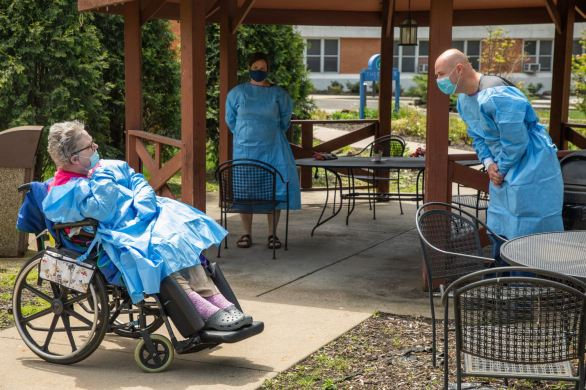 Jacob Albertson, right, and his sister Bernadette Brenkus visit their mother Debra Albertson, a resident of Brighton Rehabilitation and Wellness Center, in a pavilion outside the nursing home, Monday, May 18, 2020, in Brighton Twp. (Andrew Rush/Post-Gazette)