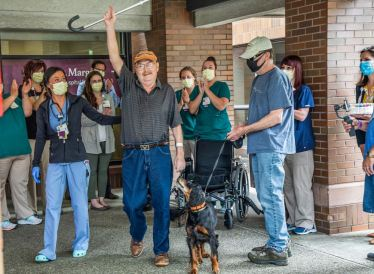 Fred Szoch, 69, walks out of St. Margaret's Hospital after reuniting with his dog Brook after 75 days of battling COVID-19, including 21 on a respirator, Monday, June 15, 2020, in Aspinwall. (Andrew Rush/Post-Gazette)