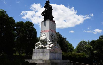 """Words like """"genocide"""" and """"murder"""" are seen on the vandalized statue base of Christopher Columbus, Friday, June 12, 2020, in Schenley Park in Oakland. In October later in the year, Mayor Bill Peduto officially recommended the statue be removed after Pittsburgh's Art Commission unanimously recommended that the statue be taken out of the park. (Darrell Sapp/Post-Gazette)"""