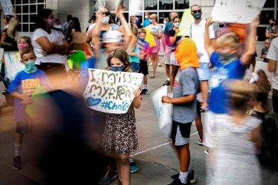 Elle Anderson, 8, of Mt. Lebanon, who will be in 2nd grade this year, holds a sign as other protesters move around her, Wednesday, Aug. 12, 2020, in Mt. Lebanon. The protestors called for the Mt. Lebanon school board to reopen schools allowing parents to chose between in-person classes and remote learning. (Alexandra Wimley/Post-Gazette)