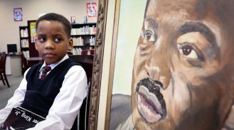 Tyrone Cleveland, a second-grader at Martin Luther King, Jr. Academy for Boys, looks at a portrait of the civil rights leader in the school's library. The Blade/Andy Morrison