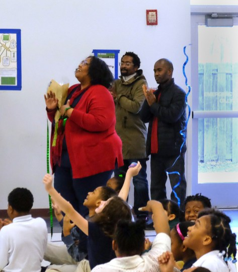 """Teacher Ellis McGee, left, after she is announced as the winner. She says she doesn't teach to receive awards: """"My award is student growth"""", says McGee. At center is her brother-in-law Jimel (cq) Jones, and her husband Larry McGee, all of Toledo. Winterfield Venture Academy holds an assembly at the primary school in Toledo, Ohio on March 12, 2019. At the assembly it is announced that Ellis McGee, fourth-grade teacher at Winterfield, has won the National Heritage AcademiesÕ annual Excellence in Teaching (EIT) Award. THE BLADE/JETTA FRASER CTY teachingaward13"""