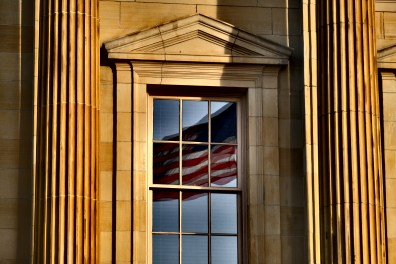 The American Flag is reflected in the window of the Federal Courthouse Wednesday, March 27, 2019, in Toledo, Ohio. THE BLADE/JEREMY WADSWORTH