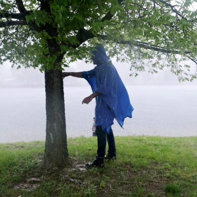 Sylvania resident Mike Romano, who was fishing, shields himself from a torrential downfall at Orlander Park on Sunday, May 19, 2019. THE BLADE/LORI KING