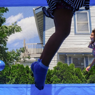 At right, Makayla Jackson, 6, jumps inside a bounce house during Party in the Parking Lot Tuesday, June 25, 2019, at the Birmingham Branch Library in Toledo, Ohio. Adaliyah McClain's, 6, feet are in the air in front.THE BLADE/JEREMY WADSWORTH