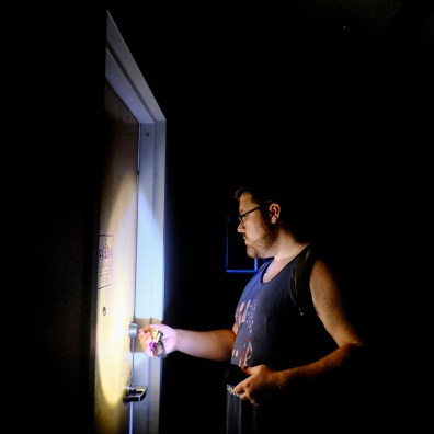 Caleb Agner uses a flashlight to navigate the dark halls to get to his apartment on the 9th floor of the LaSalle Building Tuesday, June 25, 2019, in Toledo, Ohio. The building is still without power. THE BLADE/JEREMY WADSWORTH